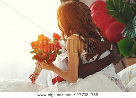 Valentine's Day. Happy Couple  With Red Hert And Flowers In Bed.