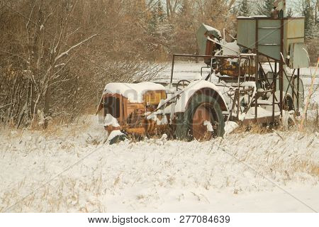 An Old And Abandoned Farm Tractor And Combine Along The Road.