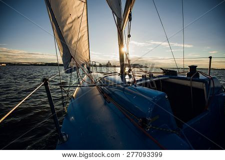 Sunset At The Sailboat Deck While Cruising Sailing At Opened Sea Or River. Yacht With Full Sails Up