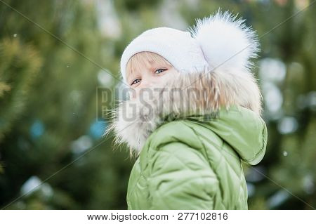 Girl playing snowballs. Funny little girl having fun in winter park. making snowballs happy child girl. winter girl throwing snowball at camera poster