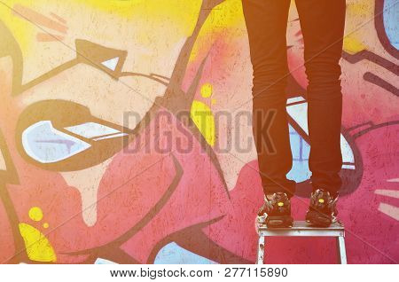 A Young Graffiti Artist Paints A New Graffiti On The Wall. Photo Of The Process Of Drawing A Graffit