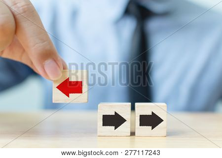 Businessman Hand Picked Wooden Block With Red Arrow Facing The Opposite Direction Black Arrows, Uniq