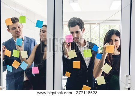 Group Of Casual Business People Planning And Brainstorm Writing Over The Project With Stickers Note