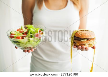 Diet. Woman Measuring Body Weight On Weighing Scale Holding Burger And Salat. Sweets Are Unhealthy J