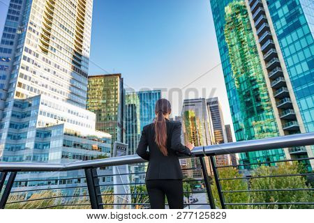 Business woman in city center looking at view of skyline skyscrapers in Vancouver downtown , Canada. Businesswoman from the back pensive thinking about success and future in career and job.