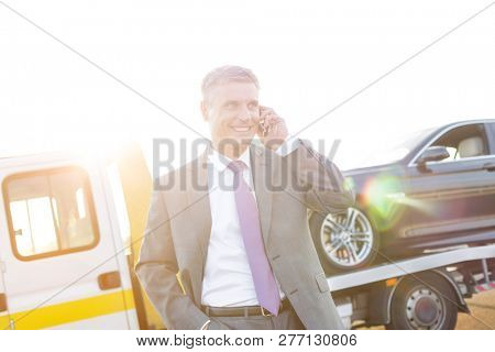 Smiling executive talking on mobile phone while tow truck picking up his car