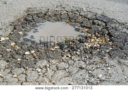 A Treacherous Pot Hole In A Tarmac Road.  Full Of Water A Loose Stones, This Pot Hole Was Created Du