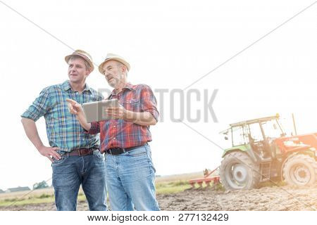 Farmers with digital tablet discussing on field against sky at farm