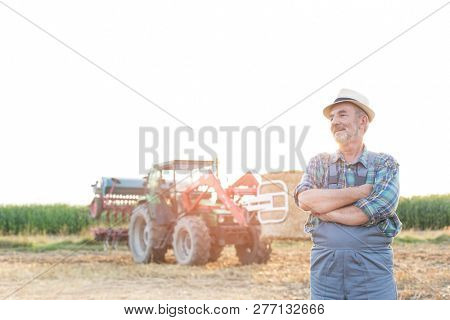 Smiling farmer standing with arms crossed against harvester at farm