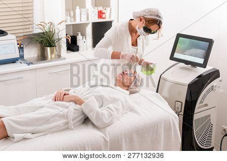 The Doctor Applies A Special Gel To The Patient. Anti Acne Phototherapy With Professional Equipment.