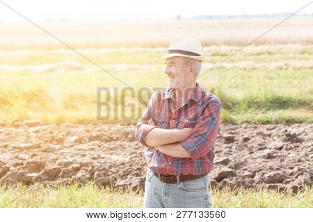 Smiling farmer standing with arms crossed on field at farm