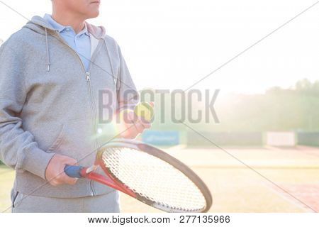 Midsection of mature man holding tennis balls and racket on court against clear sky