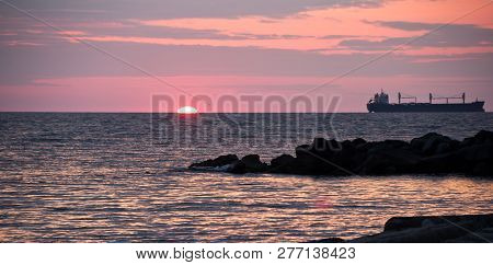 Sunset On Sea With Silhouettes Of Ships