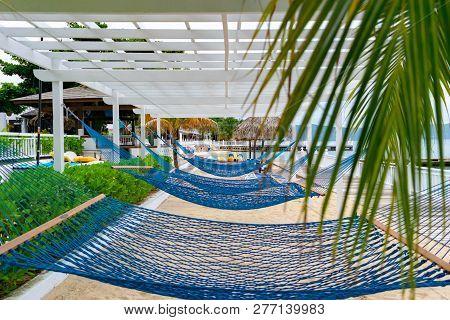 Empty Blue Hammocks On White Sand Tropical Beach Resort In The Caribbean