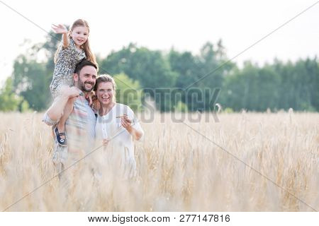Smiling parents with daughter standing amidst wheat crops at farm