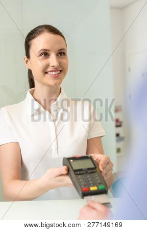 Smiling young woman making payment through credit card at checkout counter in clinic