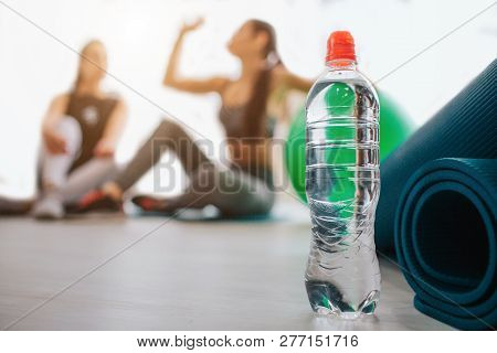 Water Bottle Stand In At Mat. Two Young Women Sit Behind. One Of Them Drink Water. Another Look At H