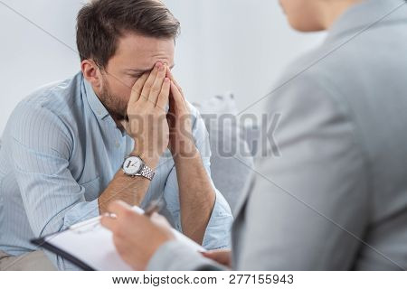 Handsome young man suffering from PTSD during session with his therapist poster