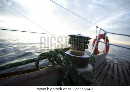 Large winch with line wrapped around and set sail in background