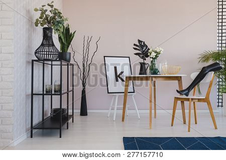 Black Mannequin's Leg On Wooden Chair In Elegant Dining Room Interior With Copy Space On The Empty W