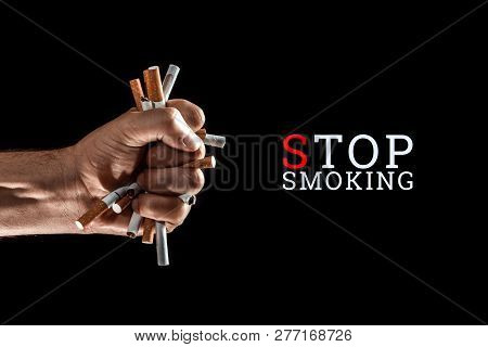 Creative Background, Male Hand Clenches A Fist Of A Cigarette On A Black Background. The Inscription