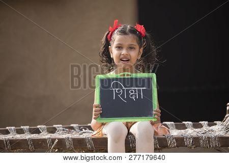 Rural Indian Little Girl Holding Slate At Home
