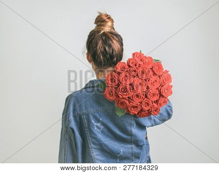 Back View Of Young Woman In Denim Jacket Holding Bunch Of Living Coral Roses On Shoulder. Girl With