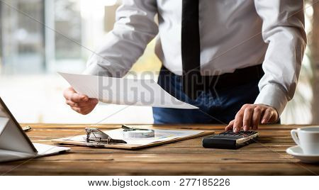 Man Working In Office And Analyzing Some Statistical Calculation Reports