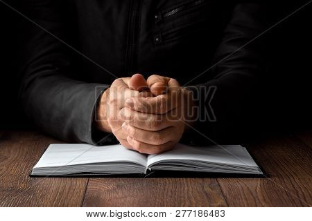 Men's Hands In Prayer On A Black Background. The Concept Of Faith, Prayer, Mourning, Forgiveness, Co