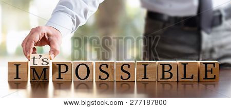 Impossible Concept With Businessman And  Wooden Blocks