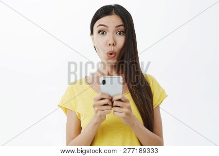 Girl Receiving Intriguing Offer Via Message Folding Lips In Wow Sound Gazing Curiously And Intereste