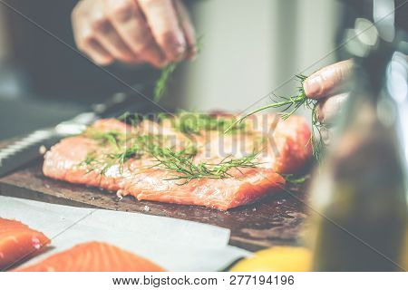 Close Up Chef Putting Salt On Salmon Slice.the Big Salmon Is In The Hands Of The Chef Cook. He Is Us