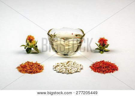 Yellow, Red Dried Petals, Inflorescences, Seeds And Oil Against A White Background. Safflower Cartha