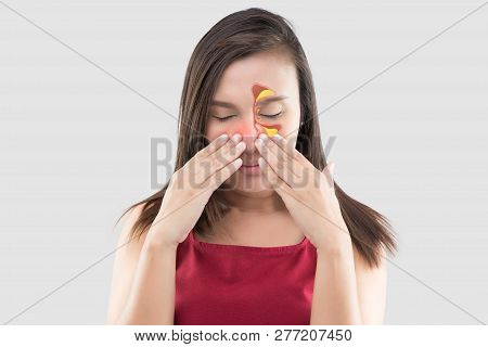 Asian Woman In Red Wear Feeling Unwell Because Of Sinus Against A Gray Background. People Caught A C