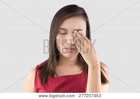 Asian Woman In The Red Shirt Has Pain In The Eye On A Gray Background, Closing Eyes With Hand, Itchi