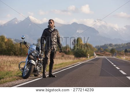 Bearded Tall Athletic Biker In Dark Sunglasses, Black Leather Clothing Standing At Modern Powerful M