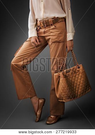 Elegant woman wearing  silk  blouse  and copper color trousers on grey.