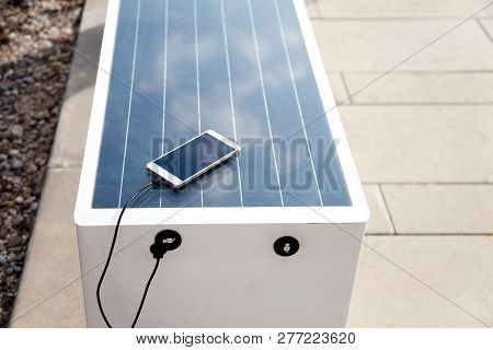 Solar Panel On Bench. Mobile Phone Charging Via Usb From Solar Power Outdoors. Alternative Electrici