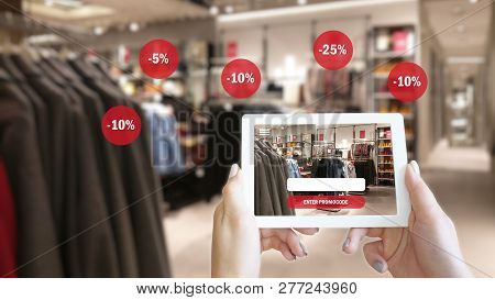 Woman Hands Taking A Tablet In Shopping Mall With Blurred Image Of Clothes Shop. The Concept Of Onli