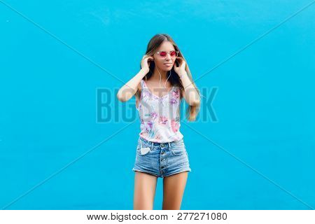 Horizontal Portrait Of Cute Stylish Girl On Blue Background Stands And Listens To Music On Earphones