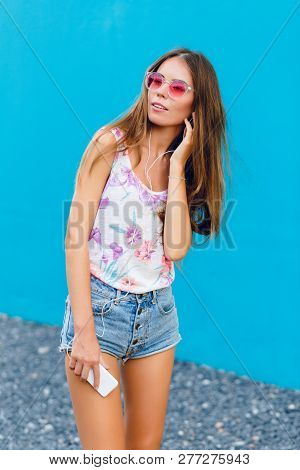 Cute Stylish Girl On Blue Background Stands And Listens To Music On Earphones On Smartphone. Girl We