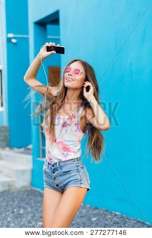 Cute Stylish Girl On Blue Background Dances And Listens To Music On Earphones On Smartphone. Girl We