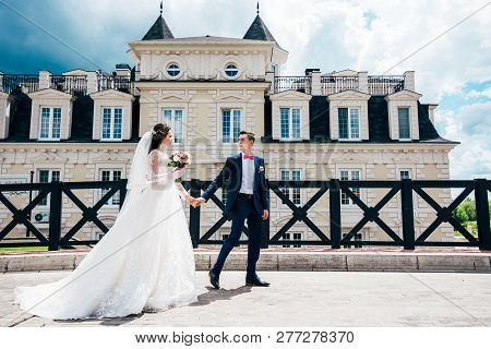 Russia, Orenburg-june 17, 2017: The Bride And Groom Holding Hands Walking Near The Beautiful Buildin