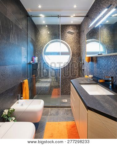 Elegant luxury bathroom with mosaic and circular window. Front view. Nobody inside