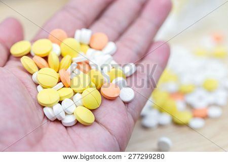 Colorful medicine pills tablets or drugs closeup in hand male. Opioid painkillers crisis and drug abuse concept. poster