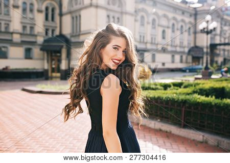 Portrait From Back Of Elefant Girl With Long Curly Hair Walking On Steer On Old Building Background.