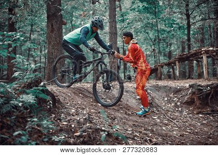 Moscow, Russia - November, 2018: MTB teacher helping rider learn to ride bicycle. Teaching a rider t