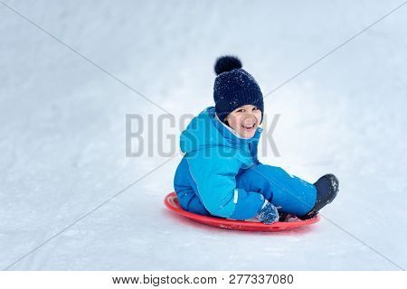 Child Rolls Down A Snow Hill. Boy Sliding Down Snow Hill In Winter. Kids Play Outside. Winter Fun Co