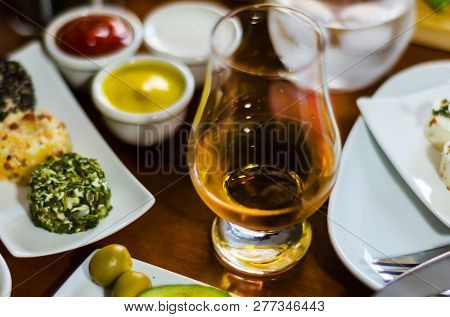 glass of whisky single malt and set with different appetizers in small portions, delicious snacks and drink poster