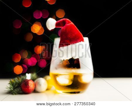 single malt  whisky in tasting glass on christmas background, colorful bokeh, xmas time poster